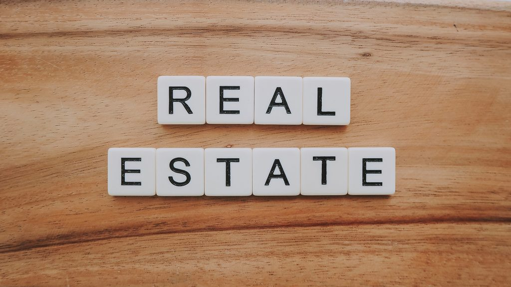 kosten makelaar op een rij, domino stenen met de tekst 'real estate'